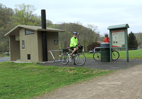 Two bikers on the trail near a rest stop